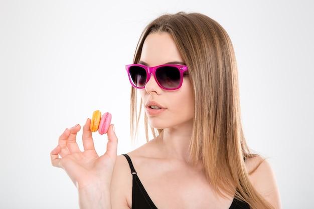 Zbliżenie pięknej zmysłowej skoncentrowanej młodej dziewczyny w różowych okularach przeciwsłonecznych, patrząc na kolorowe makaroniki