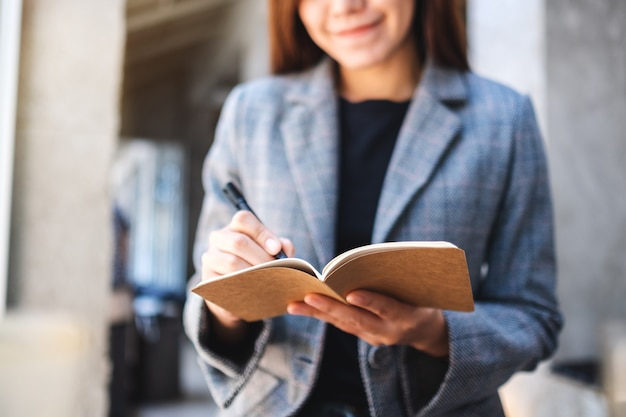 Zbliżenie piękny azjatykci bizneswoman trzyma i pisze na notatniku