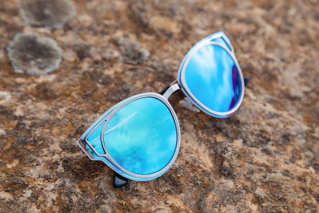Zbliżenie piękny błękitnej zieleni okularów przeciwsłonecznych odzwierciedlający pozafioletowy na ziemi w świetle słonecznym przy zmierzchem, odbicie kamienie, wapień, winnica. modne akcesoria do strzelania do sklepu optycznego