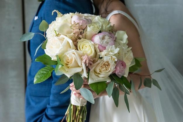 Zbliżenie piękny bukiet kwiatów w dłoni panny młodej