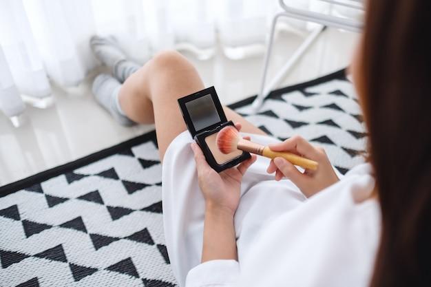 Zbliżenie piękny kobiety stosować uzupełniał proszek z muśnięciem w sypialni