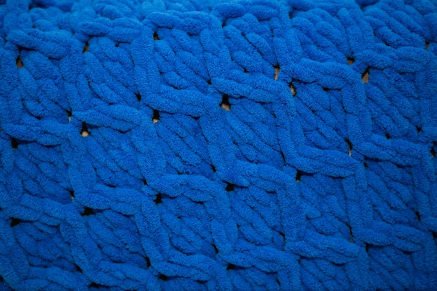 Zbliżenie, piękny niebieski pluszowy koc wełniany z piękną dzianiną, koncepcja ciepła i przytulności, miejsce na napis.