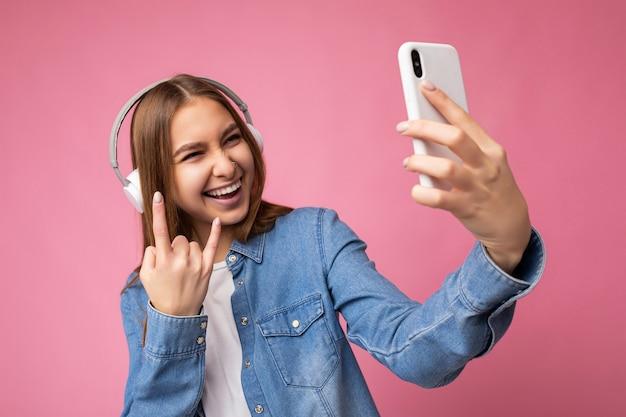 Zbliżenie piękny pozytywny śmiejąc się młoda ciemna blondynka na sobie niebieską koszulę jean stylową
