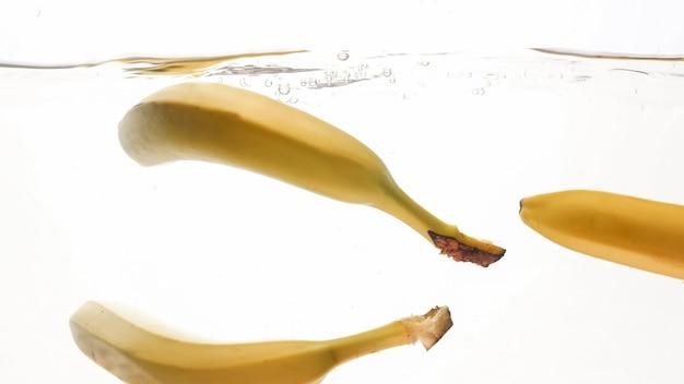 Zbliżenie piękny wizerunek bananów spadających w jasnej wodzie przeciw białemu tłu, mnóstwo powietrza unoszących się bąbelków powietrza i pluśnięcia wody