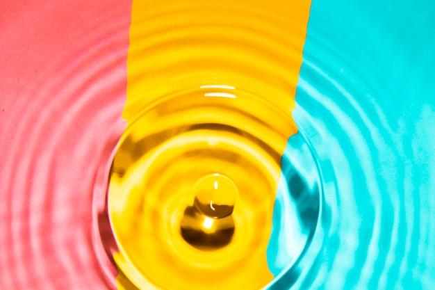 Zbliżenie pierścienie wodne z kontrastowym tłem i kroplą