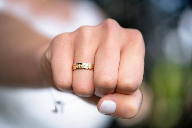 Zbliżenie pięści kobiety z obrączką na jej palcu serdecznym