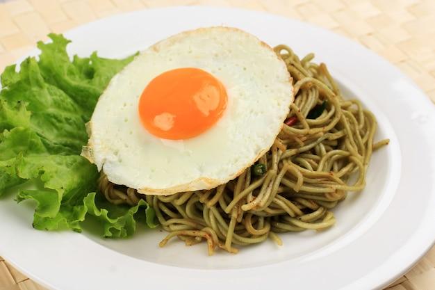Zbliżenie pikantny, zdrowy, zielony, smażony makaron błyskawiczny z błyszczącym jajkiem po stronie słonecznej i sałatą na białym ceramicznym okrągłym talerzu.