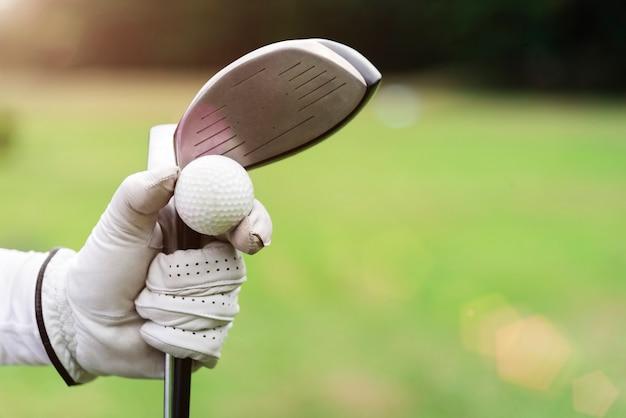 Zbliżenie piłka golfowa i kij golfowy na ręce z rękawiczką z zamazanym gr