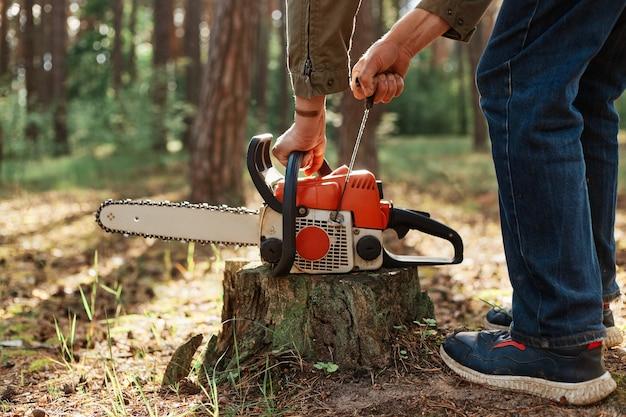 Zbliżenie piły łańcuchowej na drewnianym pniu, bez twarzy drwal zaczyna piłę