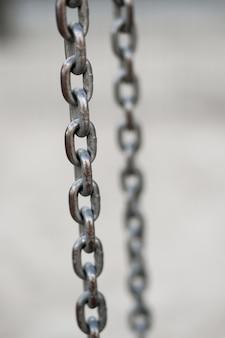 Zbliżenie pionowe strzał metalowego łańcucha na niewyraźne