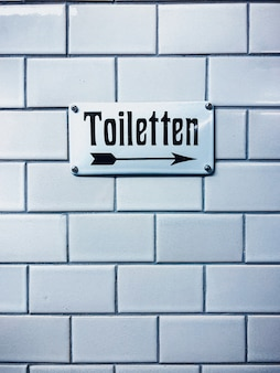 Zbliżenie pionowe strzał znak wc z niemieckim piśmie