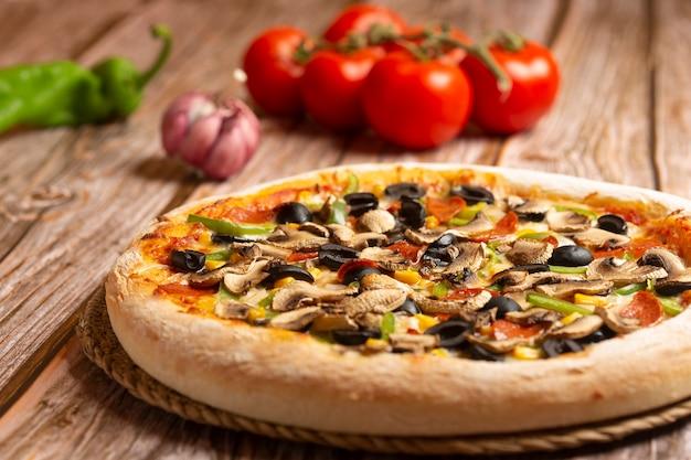 Zbliżenie pizza z warzywami i pepperoni na drewnianym