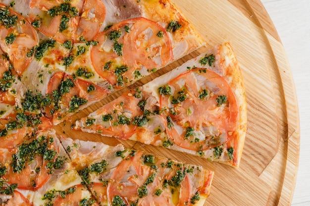 Zbliżenie pizzy na białej powierzchni drewnianych. dostawa jedzenia dla osób, które pozostają w domu