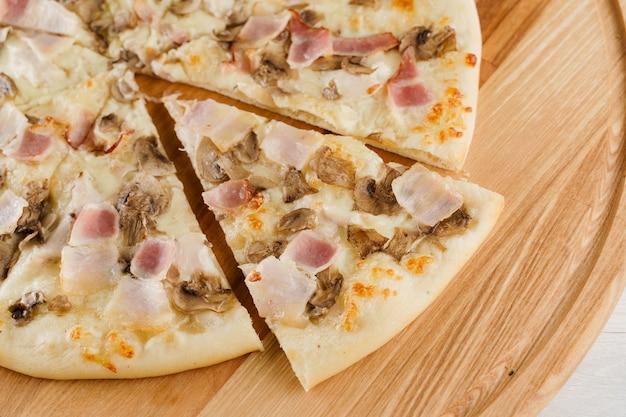 Zbliżenie pizzy na białej powierzchni drewnianych