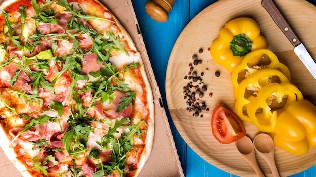 Zbliżenie pizzy z boczkiem i rukolą pozostawia w pobliżu plastry papryki; pomidor; czosnek i przyprawy na stole