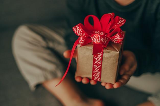 Zbliżenie planuje prezent świąteczny w rękach dziecka.