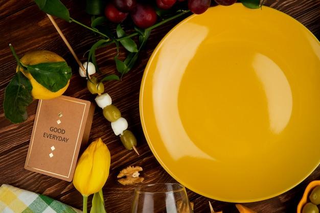 Zbliżenie plasterki parmezanu z cytryną, winogronem orzechowym i pustym talerzu na drewnianym tle