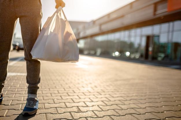 Zbliżenie: plastikowa torba wypełniona artykułami spożywczymi, warzywami i owocami spożywczymi, nabiałem. mężczyzna stoi na parkingu w pobliżu centrum handlowego lub centrum handlowego.
