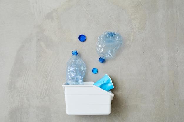 Zbliżenie: plastikowy pojemnik z odpadami na białym tle na szarym tle