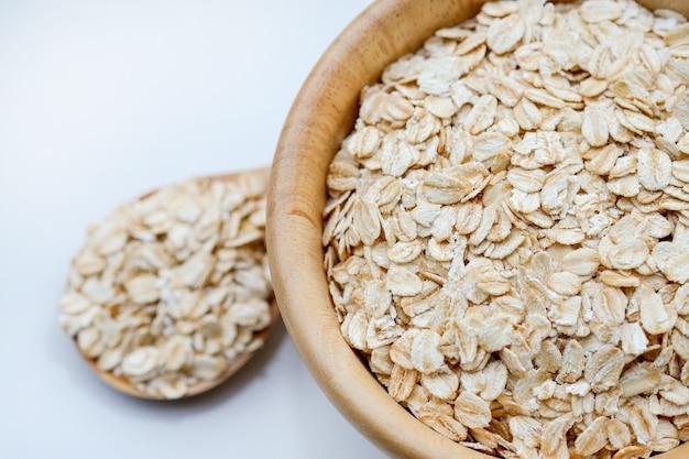 Zbliżenie płatki owsiane w drewnianej filiżance i łyżce na białym tle to zdrowe pełnoziarniste jedzenie