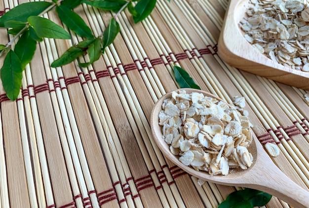 Zbliżenie płatki owsiane w drewnianej łyżce na drewnianej macie