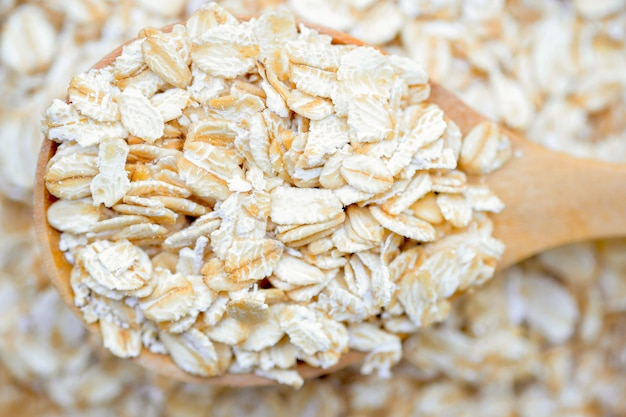 Zbliżenie płatki owsiane w drewnianej łyżce na stosie płatków owsianych to zdrowe pełnoziarniste jedzenie