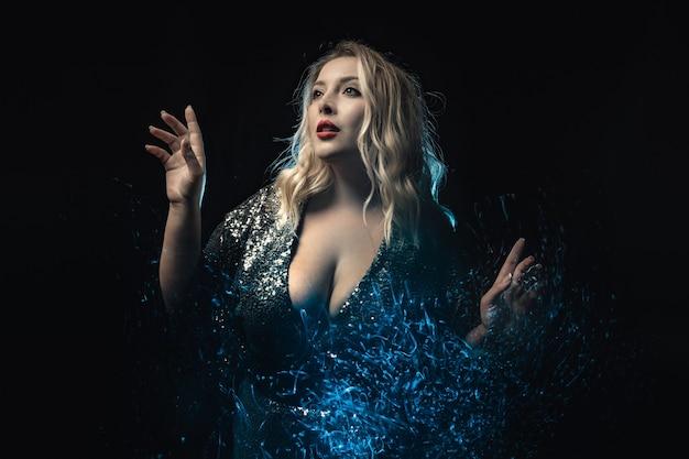 Zbliżenie plus rozmiar model w dekolt błyszcząca sukienka efekt świetlny czarne tło młoda kobieta nosi