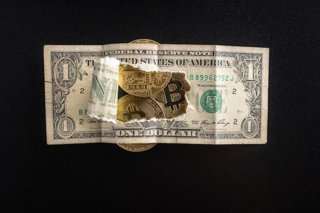 Zbliżenie: podarty banknot dolarowy, przez który widoczne są monety bitcoin. finanse i biznes