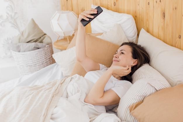 Zbliżenie podekscytowana kobieta śmiejąca się trzymając smartfon biorąc selfie zabawy z gadżetem leżącym na łóżku, ciesząc się jej wolnym czasem