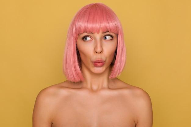 Zbliżenie podekscytowanej młodej pięknej damy z krótkimi różowymi włosami składanymi na ustach, patrząc zdezorientowanym na bok, pozując nad musztardową ścianą z nagimi ramionami