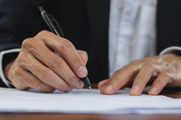 Zbliżenie podpis kierownika ręki na dokumencie, znak kontakt biznesowy w koncepcji biura