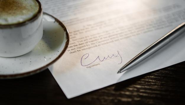 Zbliżenie podpisu. filiżanka kawy z pianką, długopis, pusta umowa na drewnianym stole.