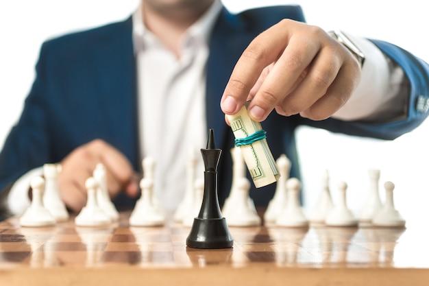 Zbliżenie pojęciowy strzał biznesmena w garniturze zrobić ruch z dolarami w grze w szachy