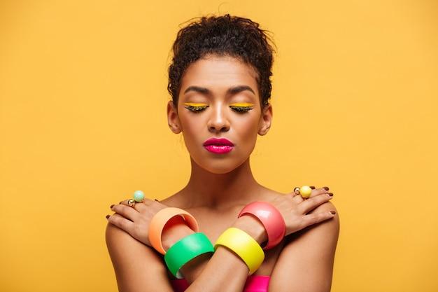 Zbliżenie pokojowa oliwkowa kobieta z zamkniętymi oczami i różową pomadką pozuje na kamerze z krzyżować rękami na ramionach, nad kolor żółty ścianą
