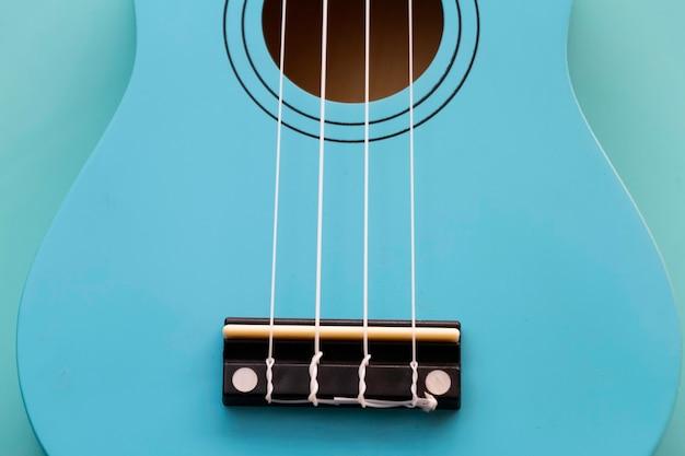 Zbliżenie połowa przedniej strony niebieskiego ukulele z białymi strunami, na pastelowym tle, instrument akustyczny