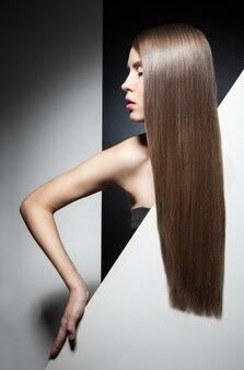 Zbliżenie połowy twarzy modelki z zamkniętymi oczami i pięknymi długimi brunetkowymi włosami