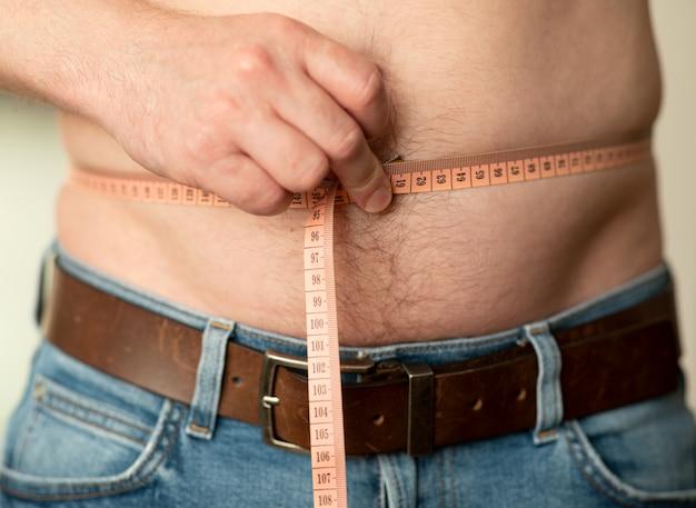 Zbliżenie pomiaru męskiego brzucha miernikiem krawieckim. mężczyzna pokazuje swój nagi brzuch