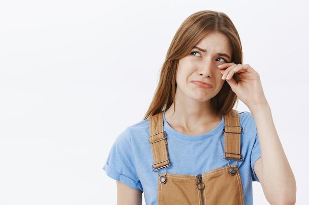 Zbliżenie ponurej płaczącej dziewczyny ocierającej łzy i smutku