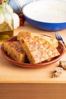 Zbliżenie porcji domowego (hiszpańskiego) omletu ziemniaczanego z naturalnymi składnikami (świeże jajka, oliwa z oliwek, ziemniaki, cebula, chorizo)