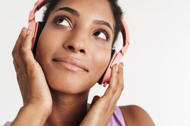Zbliżenie portret afroamerykańskiej zadowolonej kobiety za pomocą słuchawek i patrząc w górę na białym tle nad białą ścianą