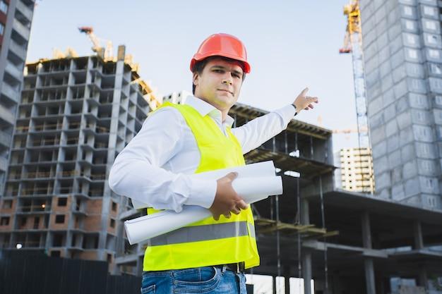 Zbliżenie portret architekta w kasku pokazujący budynek w budowie