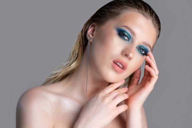 Zbliżenie portret atrakcyjna blondynka z mokrymi włosami i głęboki niebieski makijaż smokey oczy. model pozuje z nagimi ramionami na szarym tle. pusta przestrzeń