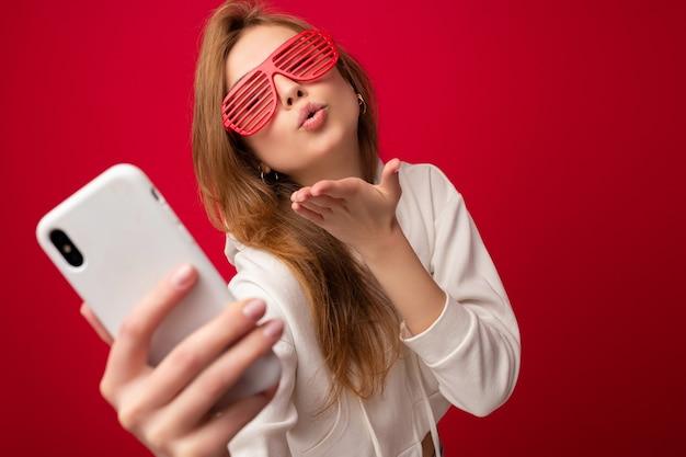 Zbliżenie portret atrakcyjne pozytywne uśmiechnięte młode kobiety blondynka na sobie stylową białą bluzę z kapturem i