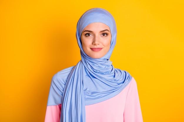 Zbliżenie portret atrakcyjnego, wesołego, skromnego muzułmanina noszącego niebieski hidżab na białym tle nad jasnożółtym kolorem tła