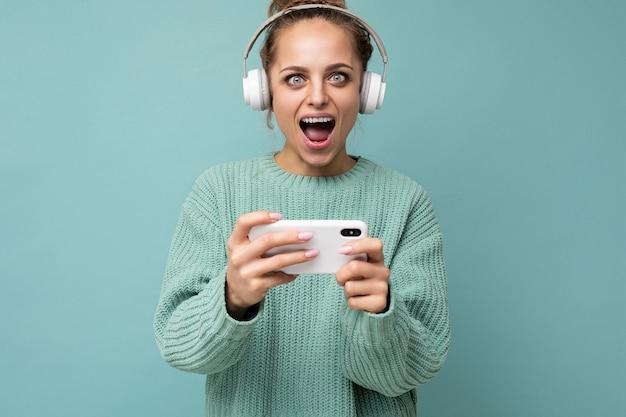 Zbliżenie portret atrakcyjnej emocjonalnej pozytywnej młodej kobiety na sobie niebieski sweter na białym tle nad