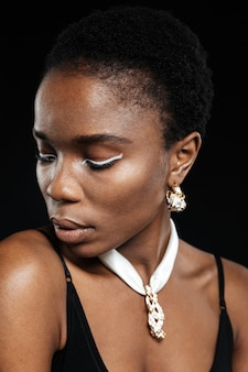 Zbliżenie portret atrakcyjnej młodej stylowej kobiety odwracającej wzrok na czarnej ścianie