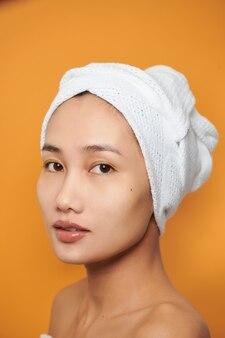 Zbliżenie portret atrakcyjnej uśmiechniętej azjatyckiej kobiety blond ubrana w ręcznik na głowie na białym tle na pomarańczowym tle, patrząc na kamery