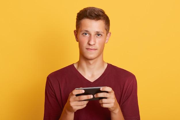 Zbliżenie portret atrakcyjny młody studencki facet jest ubranym przypadkową t koszula
