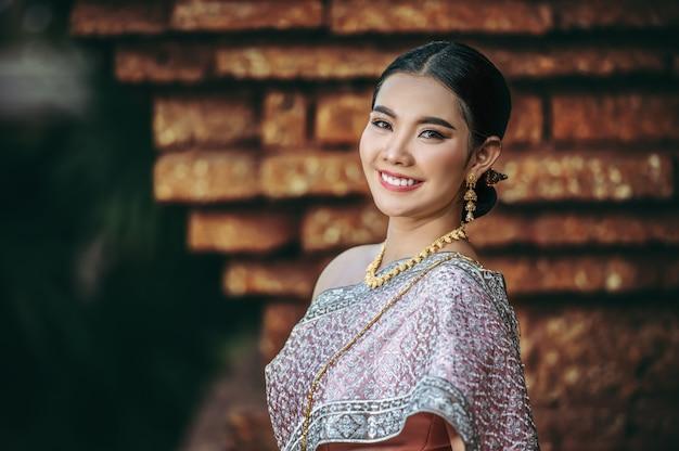 Zbliżenie, portret azjatycka urocza kobieta ubrana w piękną typową tajską sukienkę w starożytnej świątyni lub słynnym miejscu z wdzięczną pozą