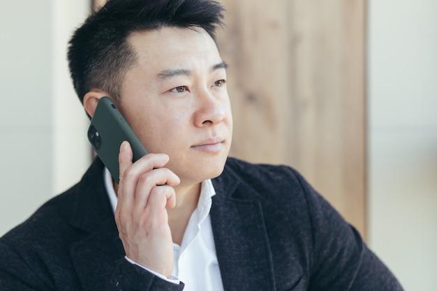 Zbliżenie portret azjatyckiego biznesmena, udana i poważna rozmowa przez telefon, w garniturze